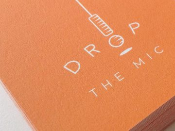 A close up of a business card featuring the Drop The Mic logo designed by Ashley Spencer